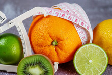 An Orange Wrapped With A Measuring Tape And A Caliper Surrounded By Fresh Fruits