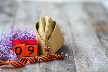 Wooden calendar with Russian text May 9, garrison cap, george ribbon and a bouquet of lilacs on a wooden background. Victory Day.