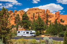 Red Canyon, UT, USA: White Rv Travels On A Tarred Road Through Red Rock Country. Pinnacles And Hoodoos Are Visible In The Background Surrounded By Pine Trees In A Sunny Summer Day