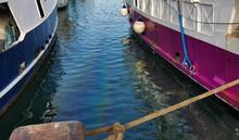Barche Da Pesca Ormeggiate E Riflessi Colorati Nell'acqua Sporca Del Porto