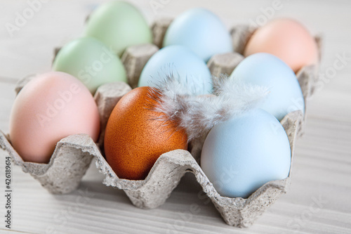 Tablou Canvas Fresh chicken organic eggs different colors and a feather in paper tray