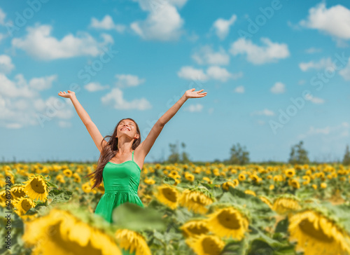 Leinwand Poster Happy free Asian woman dancing with arms up of hapiness in sunflowers field celebrating spring relaxing in the sun