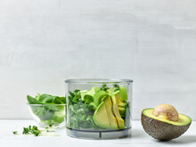 Avocado, Celery And Spinach In Plastic Transparent Blender Container