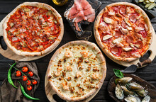 Variety Of Meat Pizzas With Sausage, Ham, Prosciutto, Salami, Chicken Fillet, Pepperoni, Shrimps, Cheese, Greens, Vegetables On Dark Wooden Background. Fast Food Lunch For Picnic Company, Top View