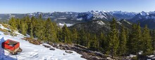 Panoramic Aerial Landscape View Of Frozen Barrier Lake, Snowy Kananaskis Range Mountain Peaks And Distant Alberta Foothills On A Sunny Springtime Day In Canadian Rockies
