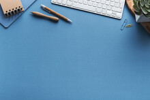 Desk With Keyboard And Wooden Supplies And Bright Blue Wall.