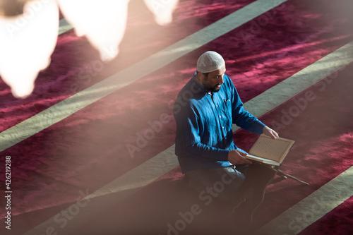 Fototapeta muslim man praying Allah alone inside the mosque and reading islamic holly book