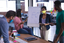 Diverse Group Of Creative Colleagues Wearing Face Masks Brainstorming In Meeting Room