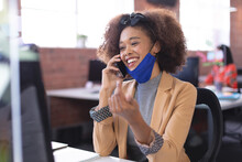 Happy African American Businesswoman Wearing Mask Talking By Smartphone In The Office