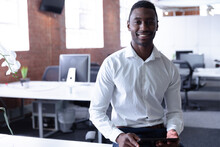 Portrait Of Smiling Casual African American Businessman Sitting On Desk With Tablet