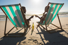 African American Couple In Love Sitting In Deckchairs, Enjoying Drinks On Beach