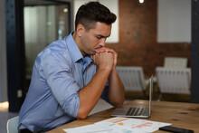 Portrait Of Stylish Caucasian Businessman Thinking, Sitting At Desk And Using Laptop