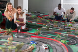 Young couples play a game slot car racing track. High quality photo