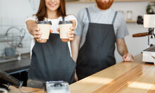 Coffee Business Concept - Positive Young Bearded Man And Beautiful Attractive Lady Barista Couple Giving Take Away Cup Of Coffee To Custome At The Modern Coffee Shop