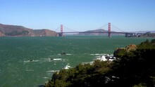 Famous Golden Gate Bridge, San Francisco California USA Landmark From Lands End Lookout. Wide Long Shot Faraway View Of Entire Golden Gate Bridge On A Windy Clear Blue Sky Summer Day