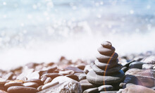 Stone Pebble Tower Balancing On The Beach With Sparkling Sea Waters Splash Bokeh. Copy Space. Balance And Mindfulness. Summer Travel And Vacation. Rainbow Reflection