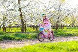 Kids on bike in spring park. Girl riding bicycle.