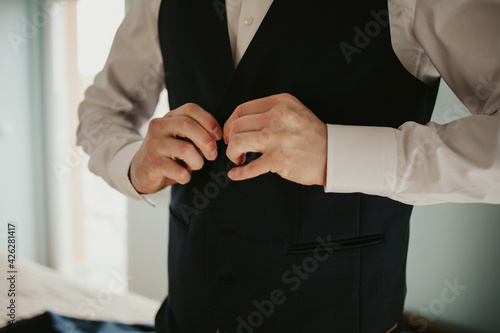 Fotografija Groom clasping the button of his waistcoat and getting prepared for his wedding