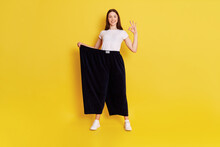 Full Length Photo Of European Lady In Huge Size Pants, Looking At Camera And Showing Ok Sign, Being Proud Of Her Results Of Loosing Weight, Isolated Over Yellow Background.