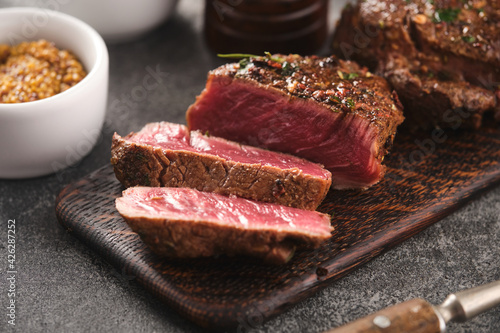 Photo Grilled beef fillet steaks with herbs and spices on wooden board