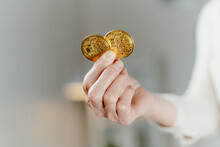 Close-up. Two Bitcoins In The Hands Of A Business Woman.