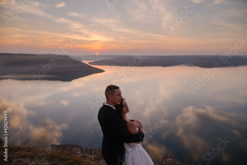 Papel de parede The groom sensual hugging bride in the mountains near the sea, amazing warm suns