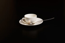 White Porcelain Coffee Cup And Saucer With Stainless Steel Spoon On Black Background