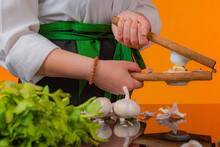 Female Chef Using A Vintage Garlic Press Along With Fresh Vegetables On Black Reflexive Glass And Orange Background.