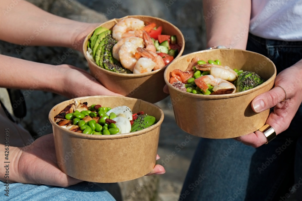Fototapeta Clean eating diet concept. Three women holding takeout bowls for different dieting habits. Disposable paper containers with healthy food. Close up, copy space, top view, background.