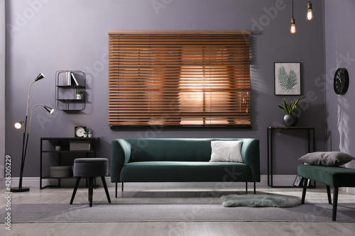 Stylish living room interior with comfortable green sofa and cushion