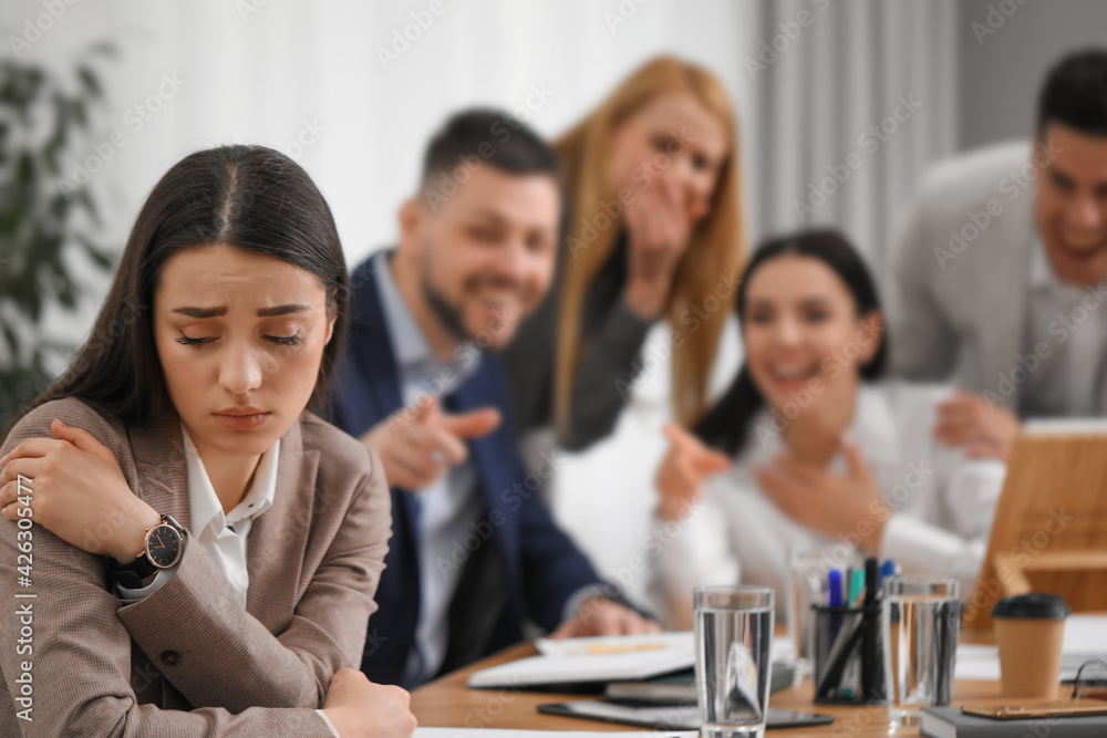 Fototapeta Coworkers bullying their colleague at workplace in office