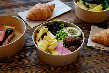 Different takeout food on wooden kitchen table. Hawaiian vegan poke bowl with variety of veggies, french croissant, salmon burger and blueberry cheesecake. Close up, top view, copy space, background.