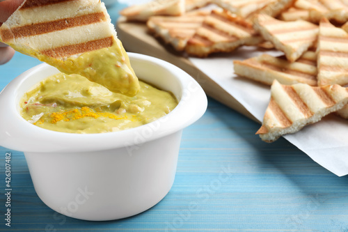 Dipping pita chip into hummus on light blue wooden table, closeup
