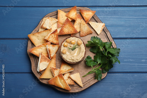 Delicious pita chips with hummus on blue wooden table, top view