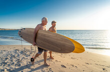 Two Senior Surfers With Surfboard Having Fun On Empty Remote Beach Enjoying Retirement Lifestyle