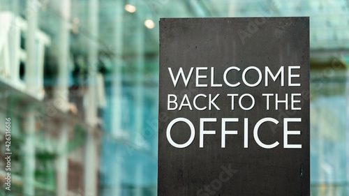 Fototapeta Welcome back to the office on a city-center sign in front of a modern office building obraz