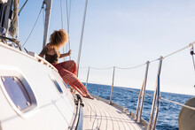 One Woman Sit Down On Sail Boat Deck Enjoy The Sea Travel Alone And Enjoy Outdoor Ocean Leisure Activity - Summer Holidays Excursions And Trip Female People - Blue Sky In Background