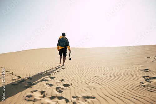 Canvas Man walking alone on desert sand dunes - explore and adventure outdoor leisure a