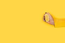 Mano De Mujer Sosteniendo Y Exprimiendo Medio Limón Sobre Un Fondo Amarillo Liso Y Aislado. Vista De Frente. Copy Space
