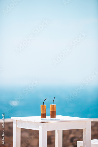 Coffee latte on wooden table with sea background