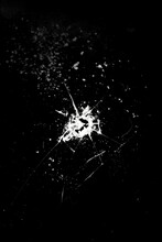 Cracked Glass, Hole And Crack On A Black Background.Broken Glass. Concept For Copy And Edit.