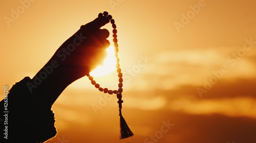 Fotografija Hand holds rosary against the sky and the setting sun, sincere prayer and medita