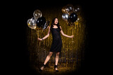 Photo of charming impressed young woman dressed black outfit holding balloons isolated gold shine backdrop background