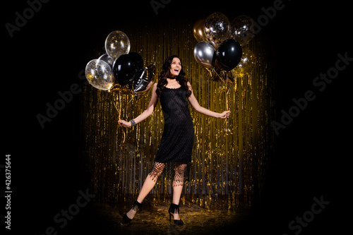 Fotografie, Obraz Photo of charming impressed young woman dressed black outfit holding balloons is