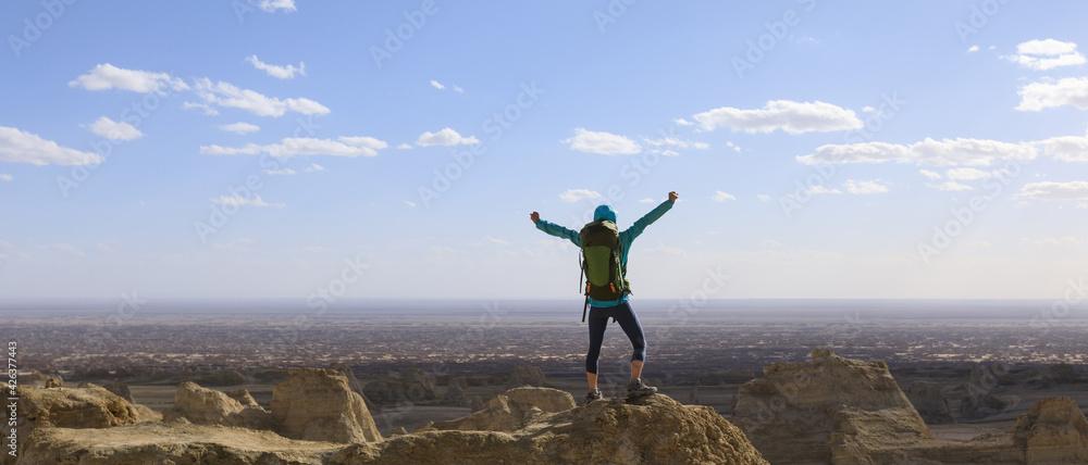 Fototapeta Successful female backpacker feel free on desert hill top