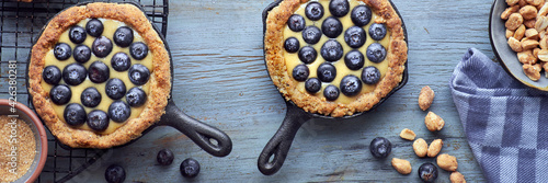 Obraz na plátně Delicious Blueberry tartlets with vanilla custard cream on woode