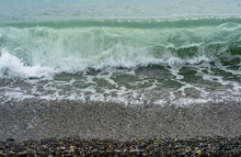 Transparent Clear Sea Wave Crest Rolling On The Pebble Coast