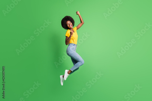 Full length body size photo of jumping girl gesturing like winner happy isolated on bright green color background