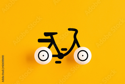 Bicycle icon made out of table tennis balls on yellow background. Environmental transportation