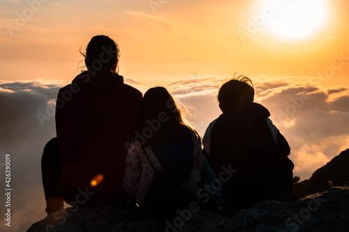 Obraz Madre e hijos disfrutando juntos del atardecer en lo alto de la montaña. - fototapety do salonu